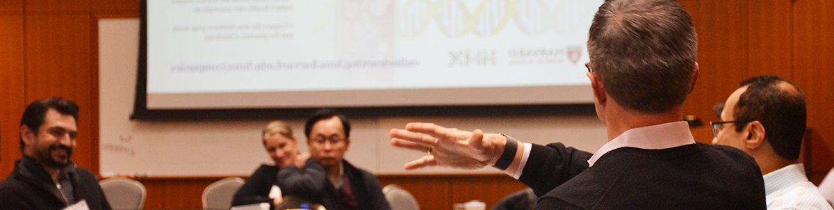 Genomics participant speaking, gesturing to peers